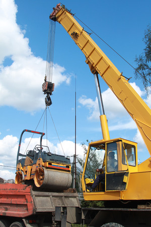 vibroroller: Loading compactor on the transportation machine using a crane   Stock Photo
