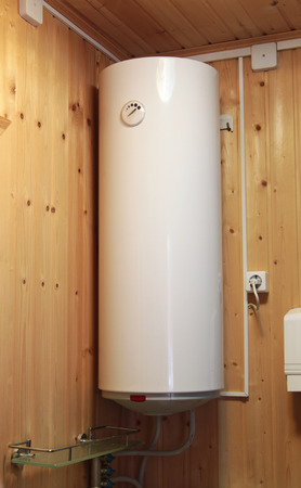 electric water heater hanging on the wooden wall photo