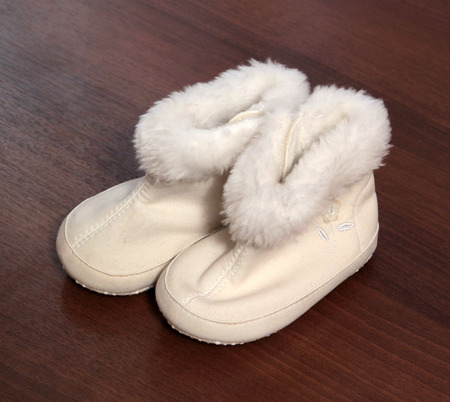 Pair of baby booties on a wooden background Stock Photo - 25764692