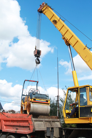 Loading compactor on the transportation machine using a crane photo