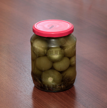 Jar of pickled physalis on a wooden background photo
