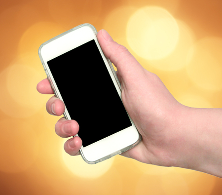 Woman hand showing smart phone with isolated screen on an abstract blurred circular bokeh lights background photo