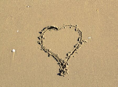 evoking: heart drawn on the sand of a beach