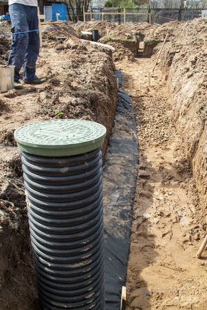 view of drainage pipes and inspection well for removal of water from a site under construction of the house