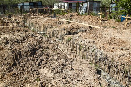 first stage of pouring the Foundation for a new building with cement and reinforcements with steel bars and wire rod