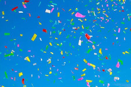 multicolored confetti on clear blue sky background