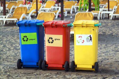Three colorful recycle bins on the beach Archivio Fotografico