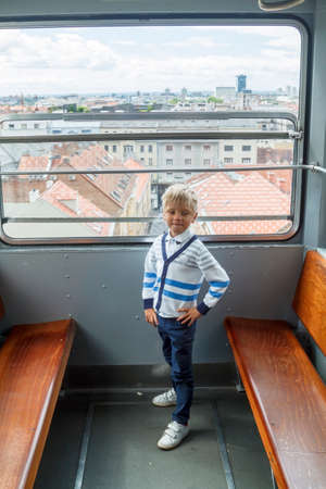 alone boy climb in an empty funicular and look at the panorama of the city of Zagreb