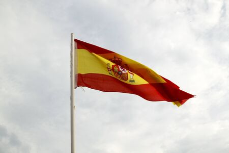 Spain flag on a blue sky with clouds background Stock Photo