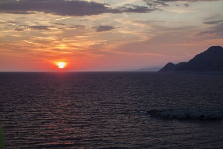 beautiful view of the sun hiding behind the sea surface in Dobra Voda, Montenegro. the sunset sky is orange with clouds and condensation traces Stock fotó