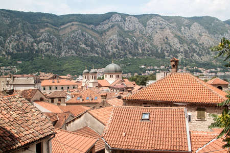 view of medieval tiled roofs of stone houses with windows and wooden shutters in the old town of Kotor, Montenegro Banco de Imagens