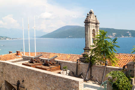 Ancient anchors and cannons stored in the Maritime Museum, an old bell tower and a stunning view of the Bay of Kotor behind it