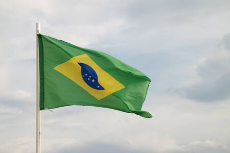 Brazilian flag on a blue sky with clouds background