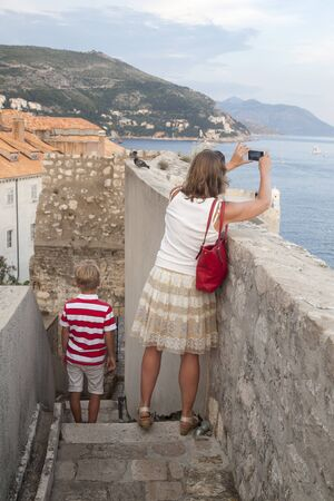 concept of cognitive recreation with children. mother traveling with her son takes pictures on the phone of the majestic views of the old city of Dubrovnik from the city wall Фото со стока
