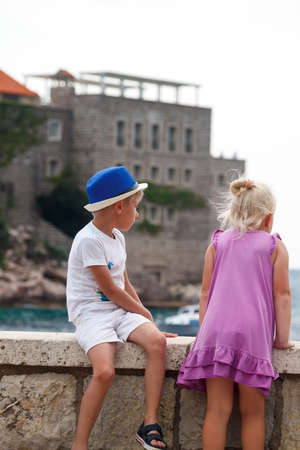 boy in a blue hat sits with his leg folded on a parapet and a girl in a pink dress stands next to him and looks thoughtfully into the distance on the sea surface