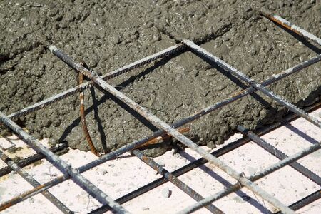 close up view of pouring concrete into prepared place with reinforced metal frame