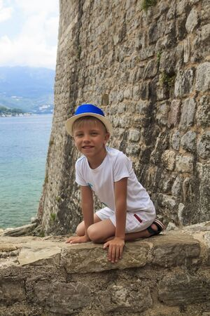 boy in a blue hat sitting on parapet of the ancient fortress of Old town in Budva, Montenegro