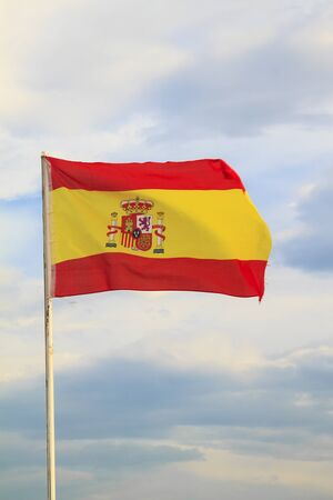 Spain flag on a blue sky with clouds background 版權商用圖片