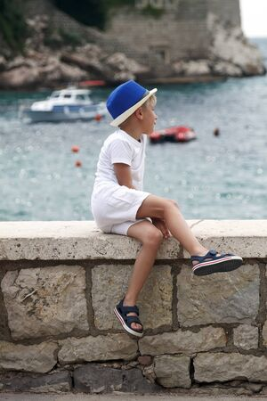 boy in a blue hat sits with his leg folded on the parapet and looks thoughtfully into the distance on the sea surface