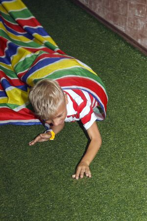 Blond boy play crawling through tube in kids zone in amusement park