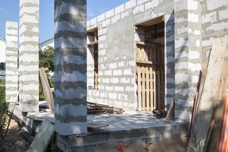 concept of alteration of construction at customer's request. Load-bearing columns made of foam block are taken out of perimeter of foundation by 10 centimeters to increase space on veranda