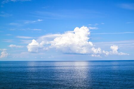 beautiful white clouds on blue sky over calm sea
