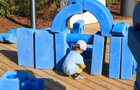 little boy is sitting on childrens playground in park with blue giant geometric figures for the development of imagination and spatial thinking