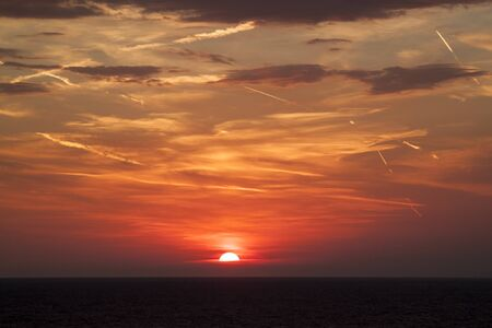 beautiful view of the sun hiding behind the sea surface. the sunset sky is orange with clouds and condensation traces