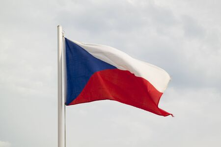 Czech Republic flag on a blue sky with clouds background