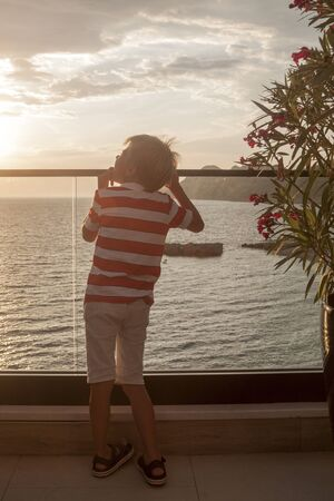 blond boy looks thoughtfully into the distance at the sea standing on the balcony at sunset