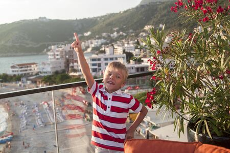 blond boy looks at the camera and threw his hand up with his index finger up standing on the balcony of a hotel near the sea at sunset
