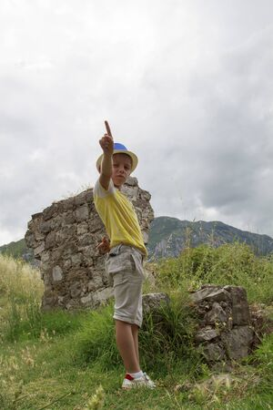 boy in a blue hat staing near ruins of the ancient fortress of Stari Bar in Montenegro Foto de archivo - 150115892