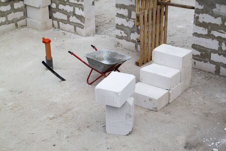 Construction site on which the walls are built of gas concrete blocks and wheelbarrow