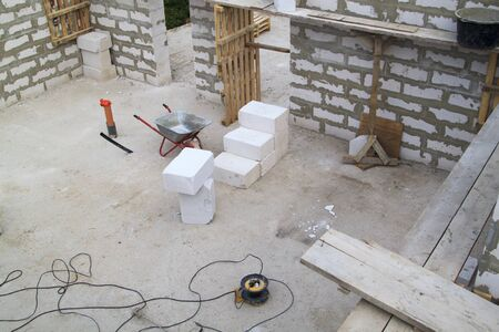 interior of a country house under construction. Site on which the walls are built of gas concrete blocks and wheelbarrow