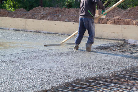 worker leveling fresh concrete slab with a special working tool Banque d'images