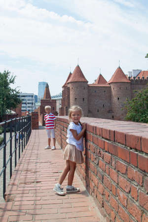 Outdoor portrait of young beautiful boy and girl posing on old street. Old Warsaw, Poland, summer Standard-Bild