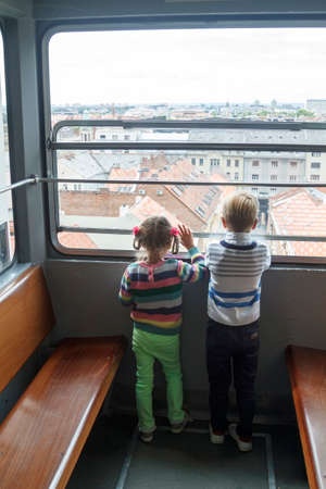 children climb in an empty funicular and look at the panorama of the city of Zagreb