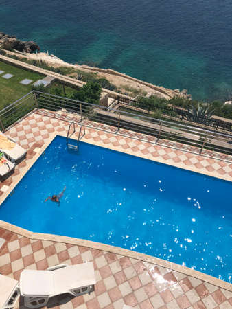 top view of a lonely little boy swimming in a large pool in a Villa standing on a rocky beach Stok Fotoğraf