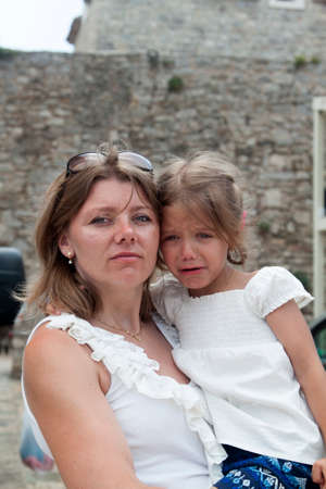 A serious and strict mother holds an alarmed girl looking into the distance against the background of an old stone wall of the color of ocher