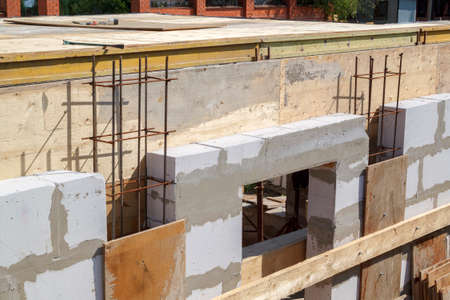 view of the wooden formwork with metal holders, which will be filled with the overlap between the floors in the country house under construction from the foam block