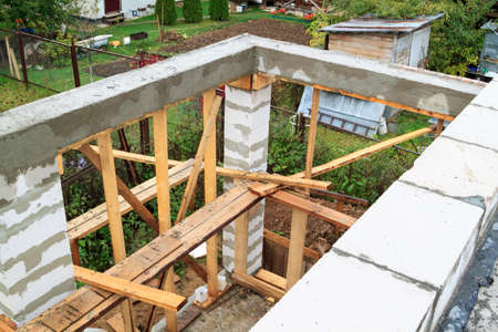 view of pit dug under foundation for a barbecue in annex to house. Site on which the walls are built of gas concrete blocks with wooden formwork 版權商用圖片