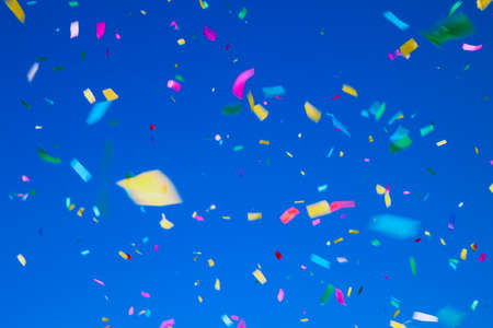 multicolored confetti on clear blue sky background. Concept of holiday backdrop