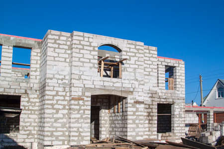 exterior of a country house under construction. Site on which the walls are built of gas concrete blocks and ladder