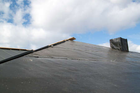 close up view of folded roof with chimney under construction on black waterproofing layer 版權商用圖片