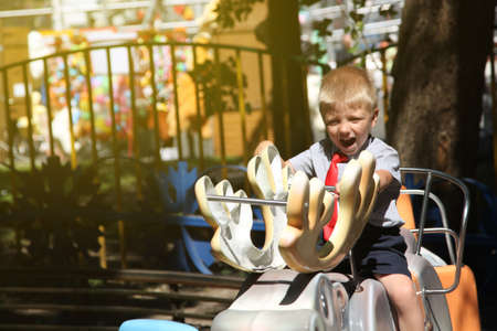 little boy with a red tie riding a carousel Stock Photo