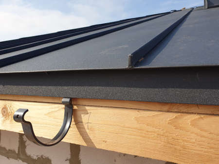 close up view of folded roof of house under construction with holders for gutters water drainage system