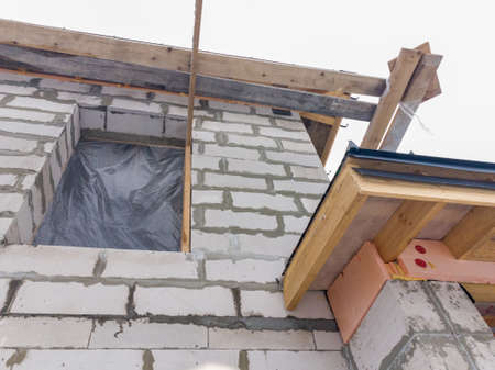 close up view of scaffolding and house under construction with gray folding roof on waterproofing layer