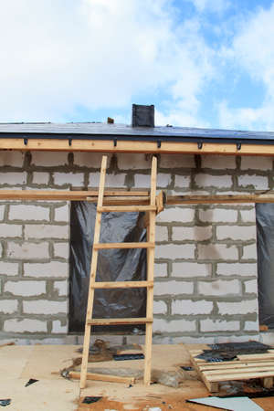 close up view of scaffolding and house under construction with holders for gutters water drainage system of roof