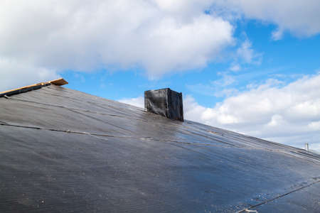 close up view of standard waterproofing layer of black color applied to protect roof and chimney from water penetration