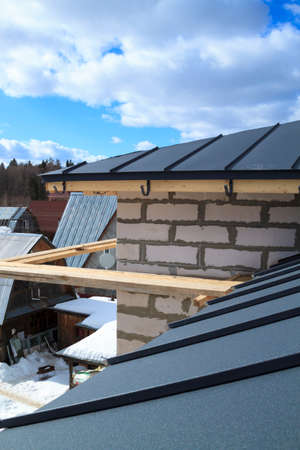 close up view of house under construction with gray folding roof on waterproofing layer